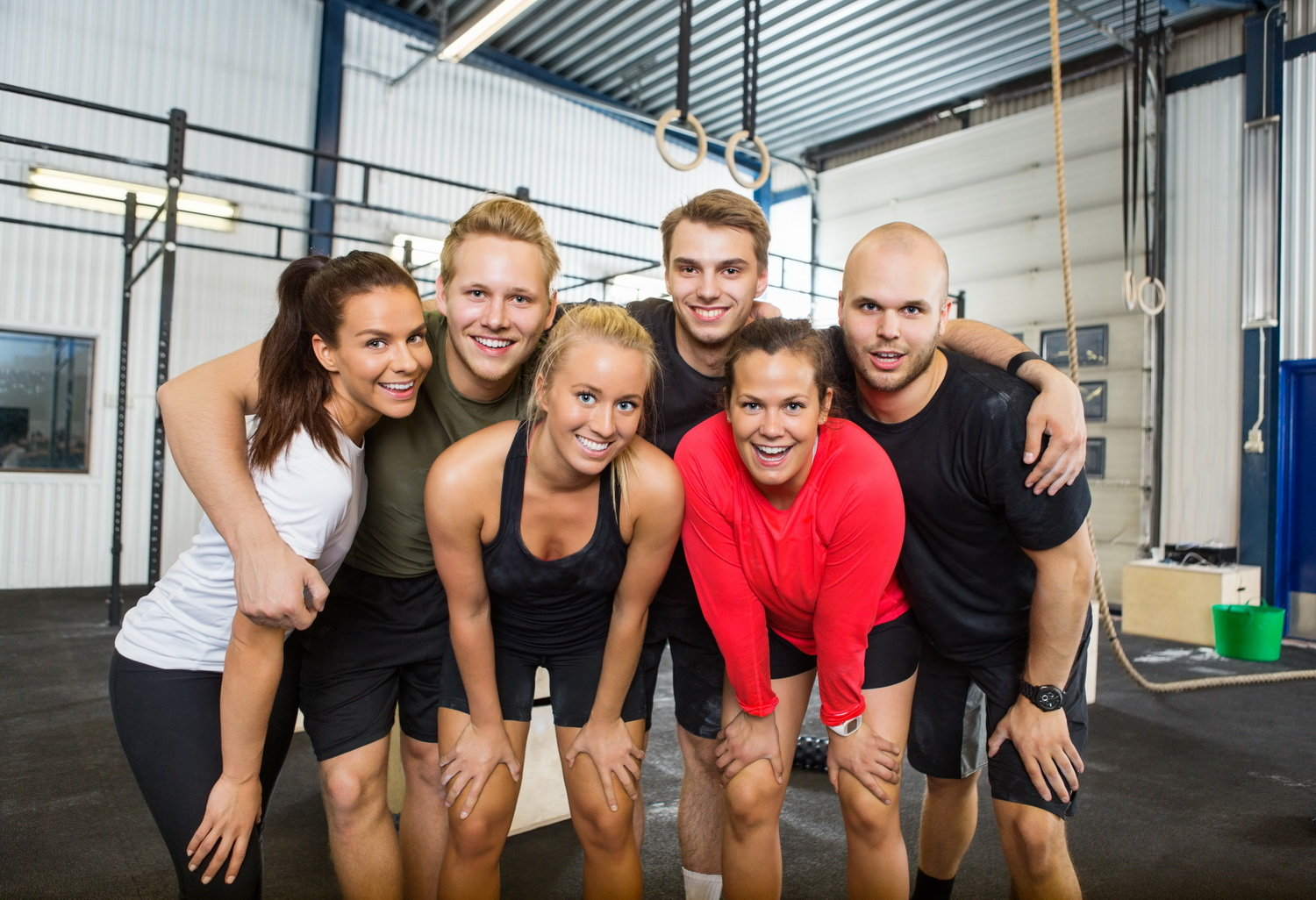 Group Of Happy Athletes Standing At cross fitness box
